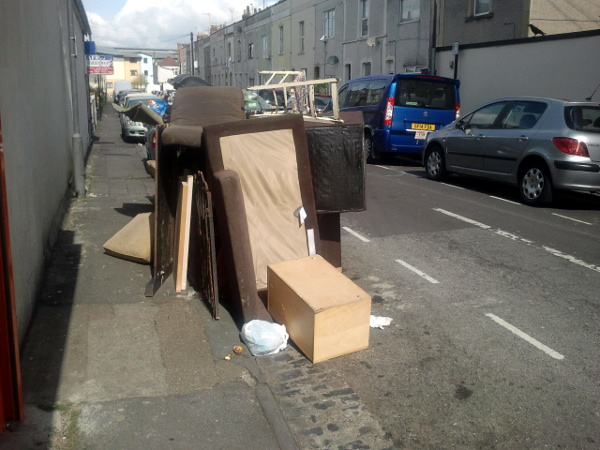 communal bin in Milsom Street buried under a pile of fly-tipped furniture